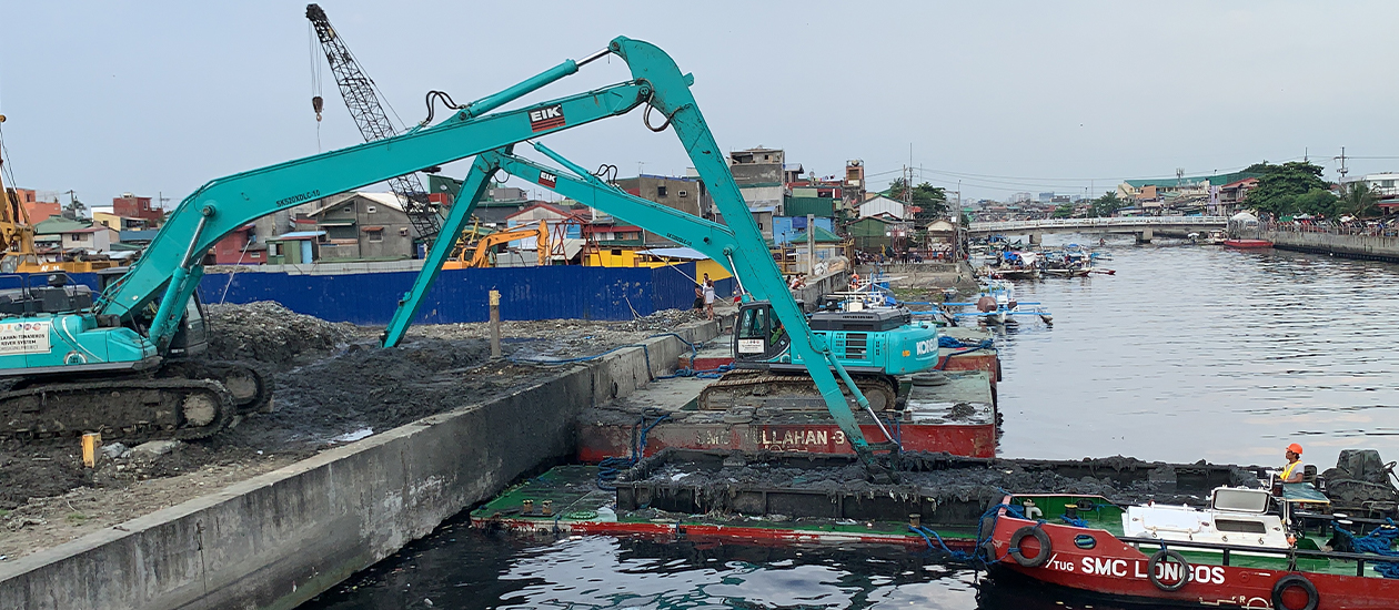 blue crane lifting garbage out of Pasig river